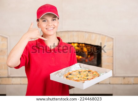 Delivery woman is holding the pizza box in hand and asking you to order pizza for delivery. - stock photo