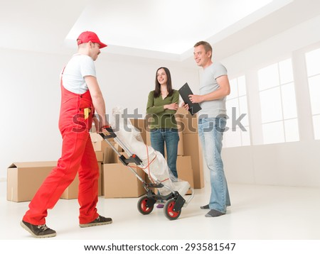 deliveryman bringing statue to young couple in new home - stock photo
