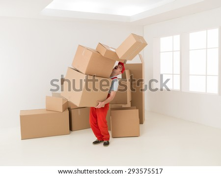 deliveryman holding stack of parcels and dropping some of them - stock photo