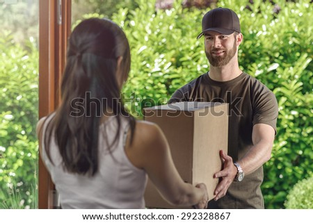 Deliveryman or postman making a door to door delivery handing over a large cardboard box to a housewife, view from behind over her shoulder of the man - stock photo