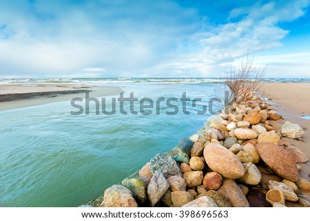 Delta  in the daytime. Rocky bank of river. The river flows into the sea - stock photo