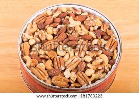 Deluxe mixed nuts in a round tin on a wood table - stock photo