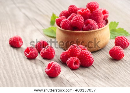 Deluxe Raspberries in bowl on wooden table. Close up, high resolution product. Harvest Concept - stock photo