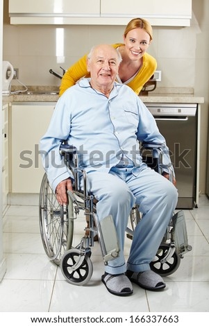 Demented senior man in wheelchair with extended care assistant - stock photo