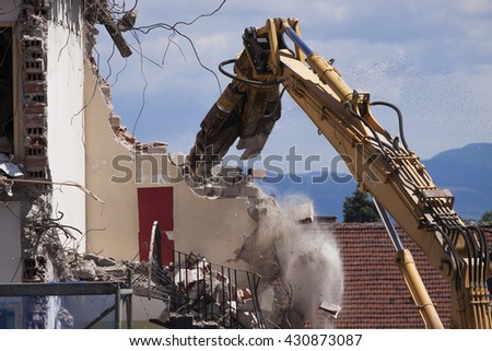 Demolition of building, Buildings with heavy industrial machine - stock photo