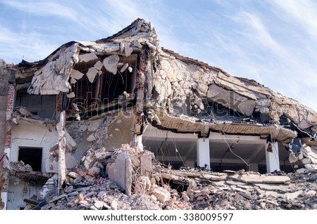 Demolition of buildings in urban environments with heavy machinery - stock photo