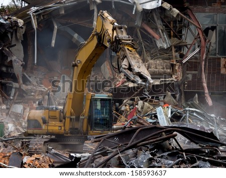 Demolition of old building by a yellow excavator - stock photo