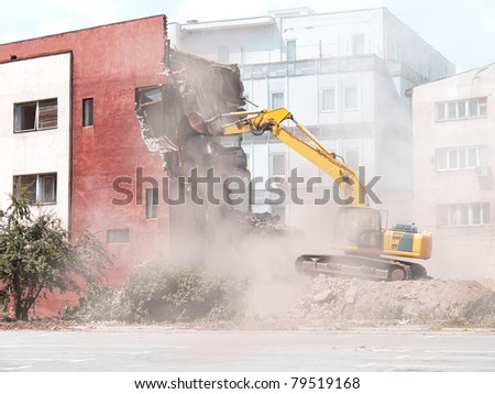 demolition of old building with bulldozer - stock photo