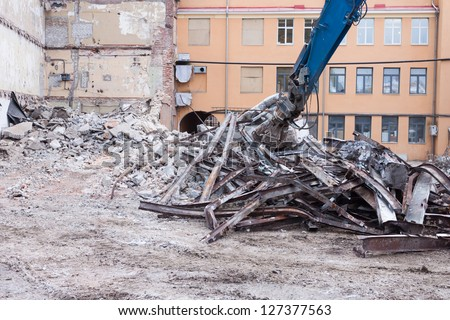 Demolition truck in action. Heap of rubble and a demolished building in the background - stock photo