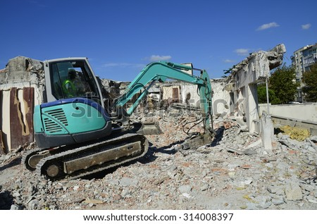 demolition with compact excavator - stock photo