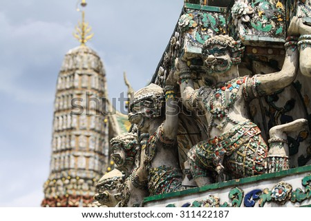 Demon Guardian statues decorating the Buddhist temple Wat Arun in Bangkok, Thailand ( selective focus ) - stock photo