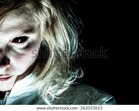 Demon-like Woman with Black Eye Looking at the Camera - stock photo
