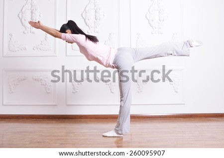 demonstration of advanced yoga pose by young attractive woman - stock photo