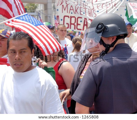 Demonstrators and LA Police Officer at illegal emigrant rally. May 1st 2006 - stock photo