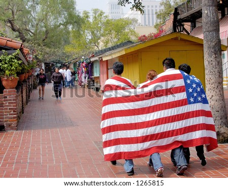 Demonstrators at Los Angeles illegal emigrant rally with US Flag. Olvera Street. May 1st 2006 - stock photo