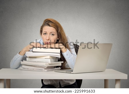 Demotivated female student sitting in at desk with pile of books and computer bored tired funny looking isolated on grey wall blackboard background. Human face expression emotion feeling bad attitude - stock photo