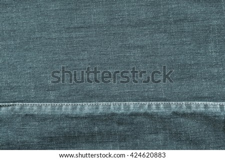 denim or rough cotton fabric or jeans material with the stitched seam for the textile textured background of pale indigo color - stock photo