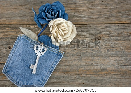 denim roses in blue jean pocket with antique key on rustic barn wood - stock photo