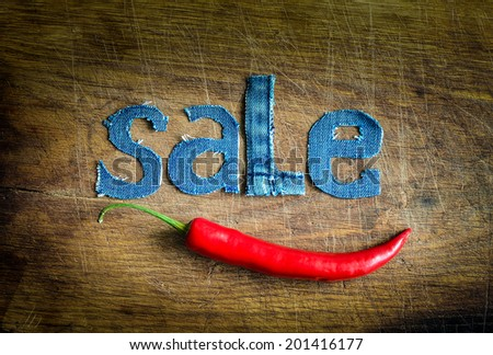 Denim sale word with red chili pepper on wooden grunge background - stock photo