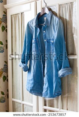 denim shirt on a hanger on the door wardrobes - stock photo