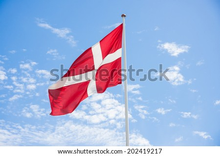 Denmark flag with blue sky background - stock photo
