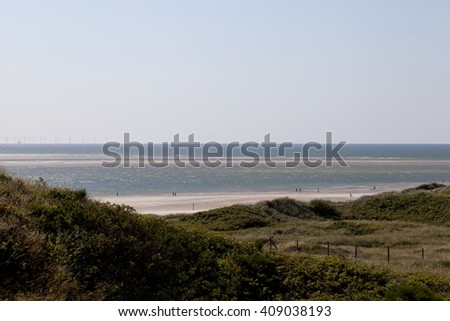 Denmark's Most Westerly Point. Looking out over the beach at Denmark's most westerly point. In the distance there is a wind farm. It is low tide and a few people are walking along the beach. - stock photo