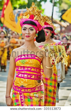 DENPASAR, BALI ISLAND, INDONESIA - JUNE 13, 2015: Beautiful woman dressed in traditional Balinese costume - sarong carrying religious offering for hindu ceremony on parade at Bali Art Festival. - stock photo