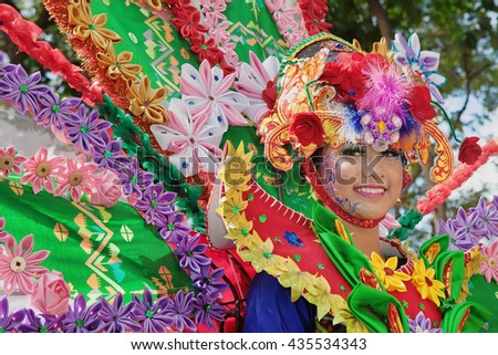 DENPASAR, BALI ISLAND, INDONESIA - JUNE 11, 2016: Face portrait of beautiful young Balinese woman in ethnic dancer costume, dancing traditional temple dance at Bali Art and Culture Festival parade. - stock photo