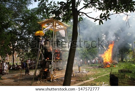 DENPASAR, INDONESIA - MAY 12:  A panoramic view of the white bull sarcophagus and pyre burning during a Balinese Ngaben or cremation ceremony in Ubud, Denpasar, Bali, Indonesia on May 12, 2013. - stock photo