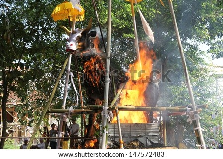 DENPASAR, INDONESIA - MAY 12:  A white bull sarcophagus burning with local village people watching during a Balinese Ngaben or cremation ceremony in Ubud, Denpasar, Bali, Indonesia on May 12, 2013. - stock photo