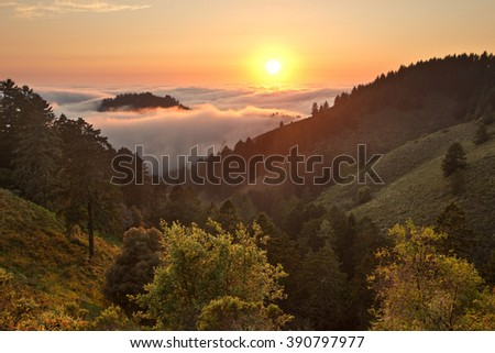 Dense fog rolls in over the Pacific Ocean at sunset over coastal California mountains - stock photo