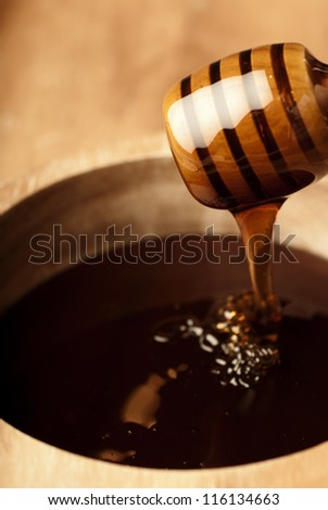 Dense honey in a wooden bowl dripping from a dripper - stock photo