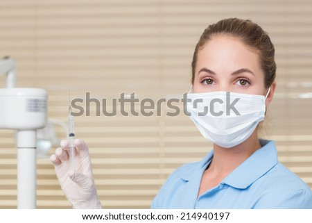 Dental assistant holding injection looking at camera at the dental clinic - stock photo