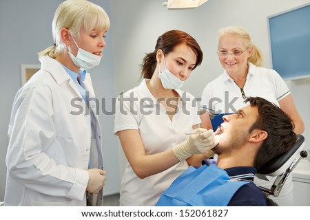 Dental assistant taking approbation test with two dentists - stock photo