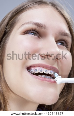 Dental Concept and Ideas.Extreme  Closeup Portrait of Caucasian Teenage Girl Brushing Teeth Brackets with Electric Toothbrush.Vertical Image - stock photo