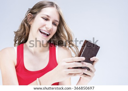 Dental Concepts and Ideas. Caucasian Female Teenager with Teeth Brackets Chatting by Cellphone. Happy Smiling. Indoors Shot. Horizontal Image Composition - stock photo