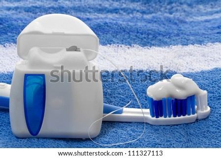 dental floss and toothbrush on a towel - stock photo