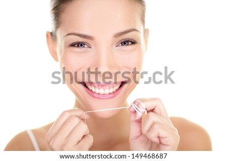Dental floss woman flossing teeth smiling happy with perfect teeth and toothy smile. Dental care hygiene concept with beautiful multiracial Asian Caucasian female model isolated on white background. - stock photo