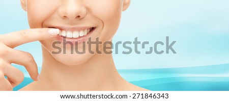 dental health, beauty, hygiene and people concept - close up of smiling woman face pointing to teeth over blue wavy background - stock photo