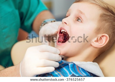 Dental inspection is being given to little boy surrounded by dentist and his assistant - stock photo
