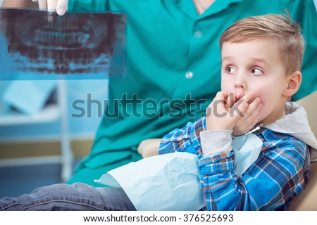 Dental inspection is being given to little boy surrounded by dentist and his assistant, showed him a photo of the teeth - stock photo