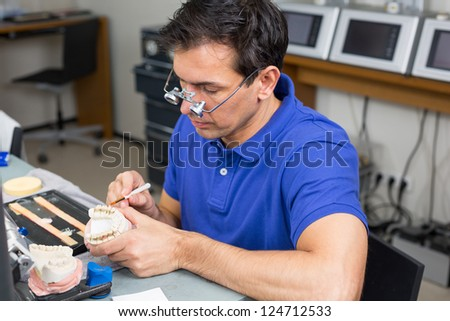 Dental lab technician with surgical loupes applying porcelain to dentition mold - stock photo