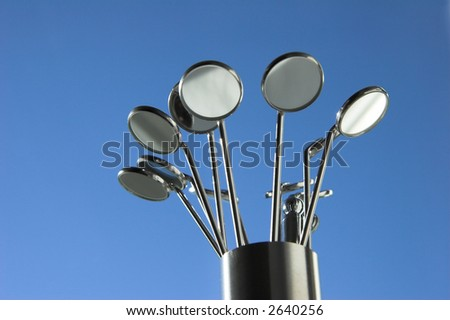 dental mirrors in their container against blue background - stock photo