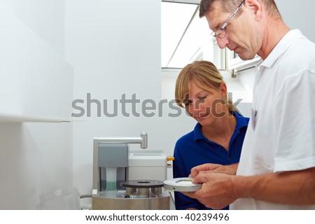 Dental technician explaining a pin drill unit - stock photo