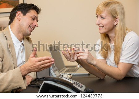Dental technician showing a model of a dental prosthesis to a customer or patient in her office - stock photo