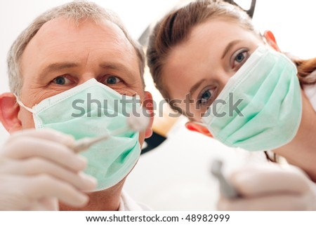 Dental treatment with dentist and dental assistant bowing over the patient as seen from patient's perspective. They have drills and angled mirrors, focus on eyes of dentist - stock photo