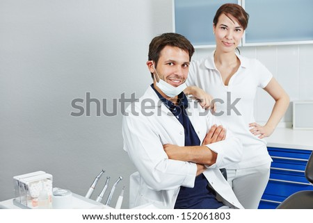 Dentist and female dental assistant together in a dentistry - stock photo