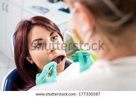 Dentist checking dental hygiene on patient in the office. Selective focus, focus on the patient. - stock photo