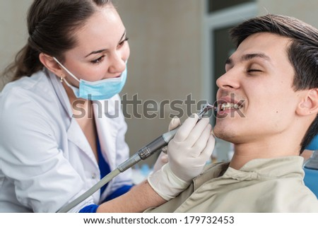 Dentist curing a male patient - stock photo