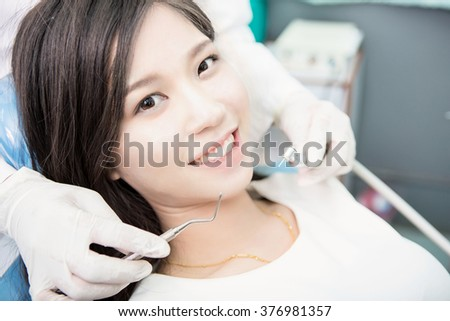 Dentist examining a patient's teeth in the dentist. - stock photo